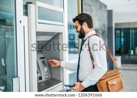 Businessman using card at an ATM