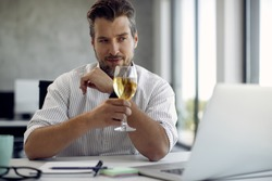 Businessman using computer and toasting with wine while dating online in the office.