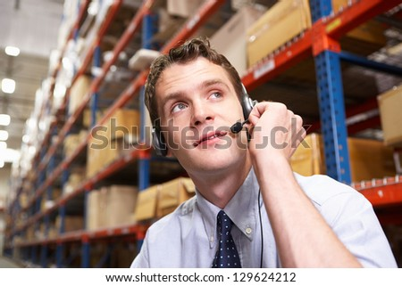 Businessman Using Headset In Distribution Warehouse - stock photo