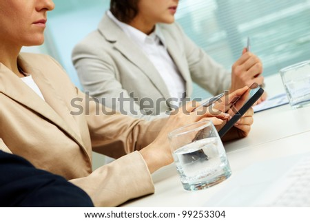 Businessman using her tablet pc, her colleagues sitting on both side of her, tilt up
