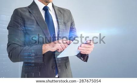 Businessman using his tablet pc against grey vignette