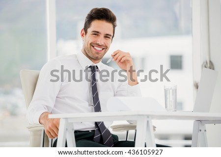 Businessman using laptop and taking notes in office