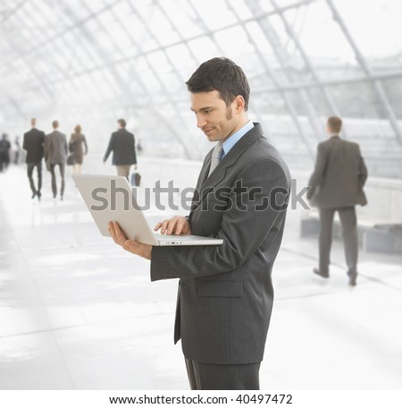 Businessman using laptop computer standing on office hallway.