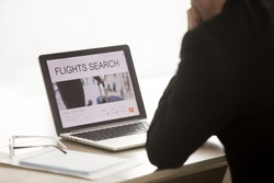 Businessman using laptop for searching cheap low cost business flight, choosing airfare deal, comparing trip prices, booking airplane ticket online on web service, focus on screen, close up back view