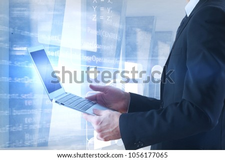 Businessman using laptop in abstract concrete interior with blurry html code. Computing concept. Double exposure  #1056177065