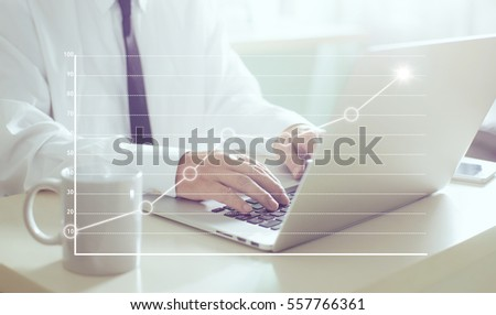 Businessman using laptop with graph statistical analysis ,Business success concept. #557766361