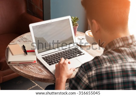 Businessman using laptop with tablet and pen on wooden table in coffee shop with a cup of coffee
