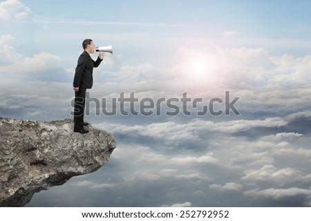 Businessman using megaphone yelling on cliff with sunlight cloudscape background
