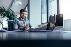 Businessman using mobile phone in the office with feet on the table. Male designer listening music in break time.