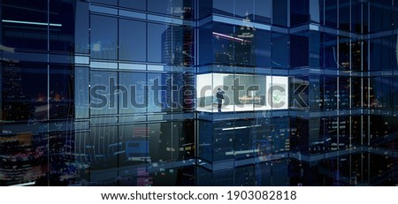 Businessman using mobile phone to talk business in office. View from the outside 3D rendering commercial skyscraper. Foto d'archivio ©