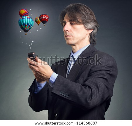 Businessman using mobile phone with touch screen with streaming images, email, multimedia symbols