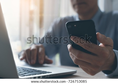 Businessman using mobile smart phone concentrate working on laptop computer in office. Man working and browsing internet on electronics devices, e business and technology concept #726753085