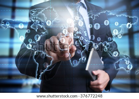 businessman using modern computer and pressing button on virtual screen with world map. global recruitment. global outsourcing. social networks.. business, technology and internet concept.