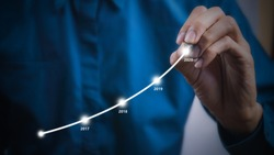 Businessman using pen drawing graphics line year growing graph.Describe the organization's management plan or Company and development guidelines. Depicts business growth up continuity plan until 2020.