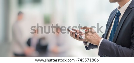 Businessman using smart phone in blurred office space background and copy space.Concept of business people use technology.
