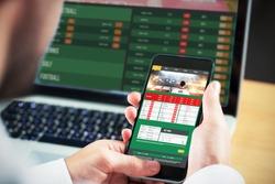 Businessman using smartphone against gambling app screen