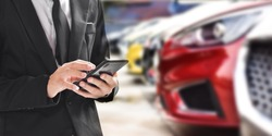 Businessman using smartphone on blurred background of new car displayed in showroom dealer with copy space.