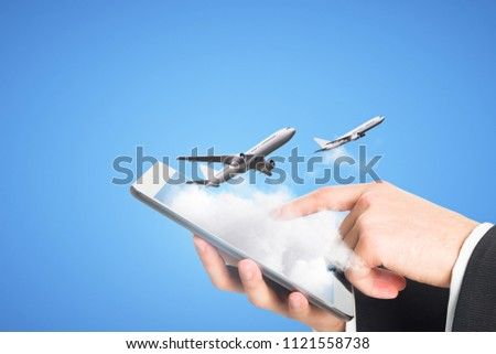 Businessman using smartphone with clouds and airplane on blue background. Online ticket purchase concept