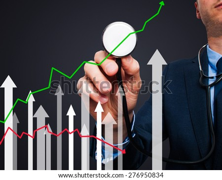 Businessman using stethoscope to diagnose business performance. Business finance, technology concept. Isolated on black. Stock Photo