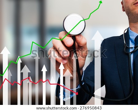 Businessman using stethoscope to diagnose business performance. Business finance, technology concept. Isolated on office. Stock Photo