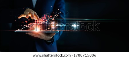 Businessman using tablet analyzing sales data and economic growth graph chart and block chain technology on global network on dark background.