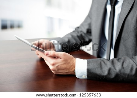 Businessman using tablet by the desk