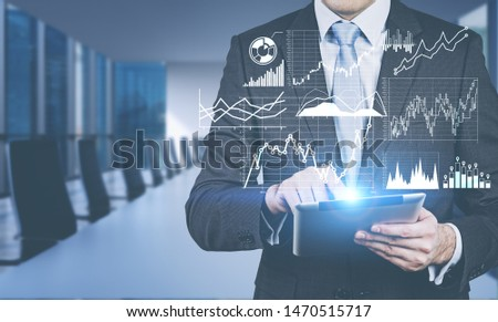 Businessman using tablet computer in blurred meeting room with double exposure of graphs and business infographics. Concept of trading and market analysis. Toned image #1470515717
