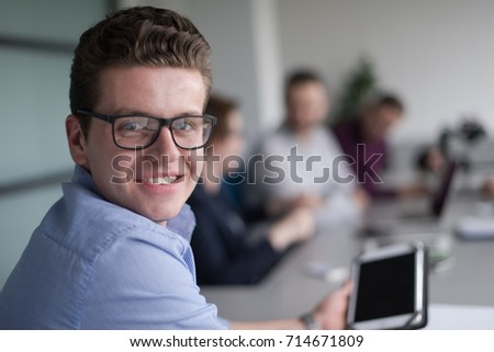 Businessman using tablet computer in office with coworkers in background #714671809