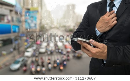 Businessman using the smart phone on abstract Blurred photo of traffic jam and world map, Elements of this image furnished by NASA #311278607