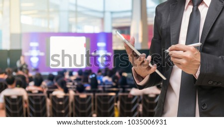 Businessman using the tablet on the Microphone over the Abstract blurred photo of conference hall or seminar room with Speakers on the stage and attendee background, Business meeting concept #1035006931
