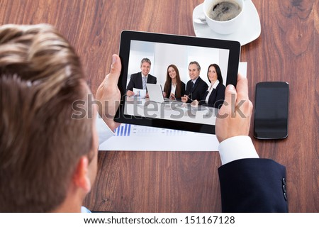 Businessman Video Conferencing On Digital Tablet In Office