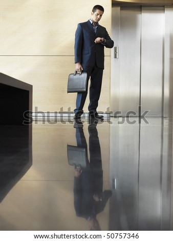 Businessman Waiting in Lobby checking wristwatch