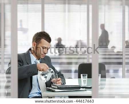 Businessman waiting in meeting room in modern, corporate office. Pouring water to glass.