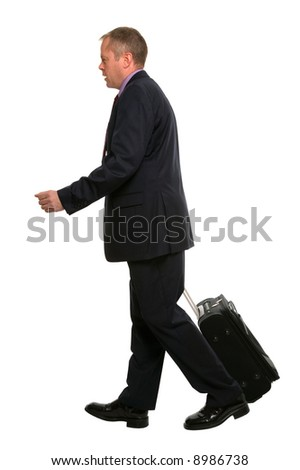 Businessman walking along pulling his travel luggage.