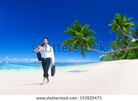 Businessman walking along the tropical beach.