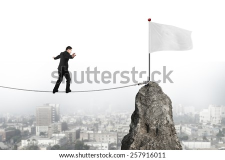 Businessman walking and balancing on rope toward white flag of mountain peak with cityscape background