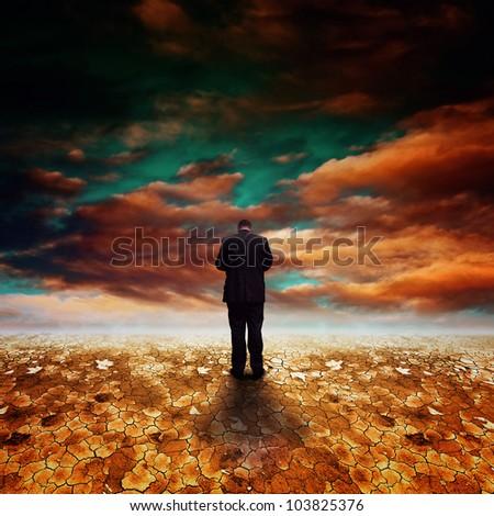 Businessman walking away into dry desert land