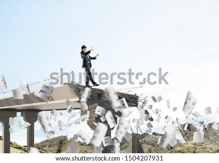 Businessman walking blindfolded among flying documents on concrete bridge with huge gap as symbol of hidden threats and risks. Skyscape and nature view on background. 3D rendering. #1504207931