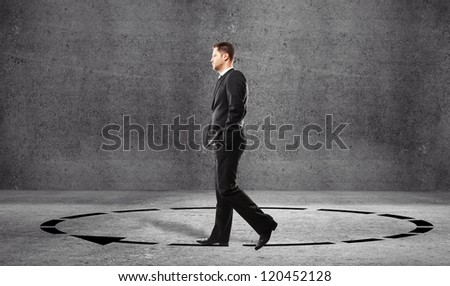 Businessman walking in a circle in room