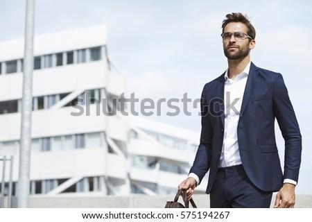 Businessman walking in city #575194267