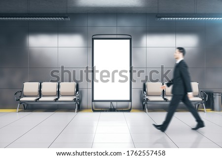Photo of  Businessman walking in metro station with blank poster on wall. Underground and urban concept. Mock up
