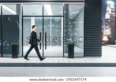Businessman walking near glass entrance in modern business center. Business and architecture concept. Mock up. Photo stock ©