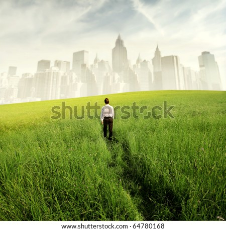 Businessman walking on a green meadow with cityscape on the background - stock photo
