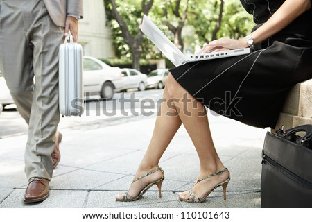 Businessman walking passed a sexy businesswoman who's using her laptop computer while sitting down outdoors.