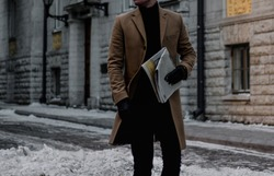 Businessman walking through the streets with newspaper, winter
