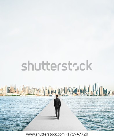 businessman walking to city on concrete bridge