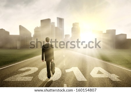 Businessman walking to the New Year 2014 with cityscape background #160154807