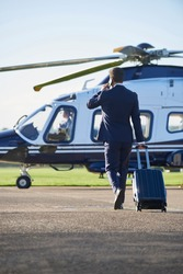 Businessman Walking Towards Helicopter Whilst Talking On Mobile Phone
