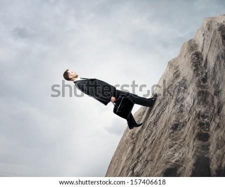 businessman walking up on rock