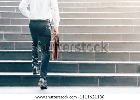 Businessman walking up on stairs and holding briefcase. Сток-фото ©